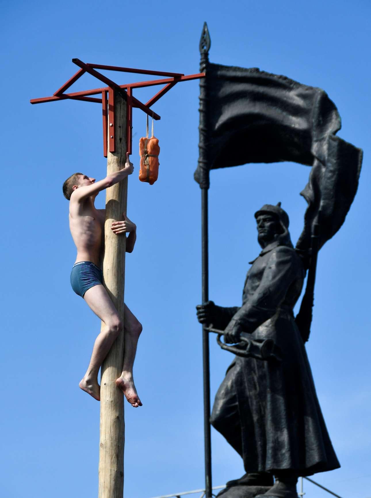 Στο Βλαδιβοστόκ, ένας ακόμη ημίγυμνος άνδρας σκαρφαλώνει σε κολόνα για να παραλάβει το βραβείο του