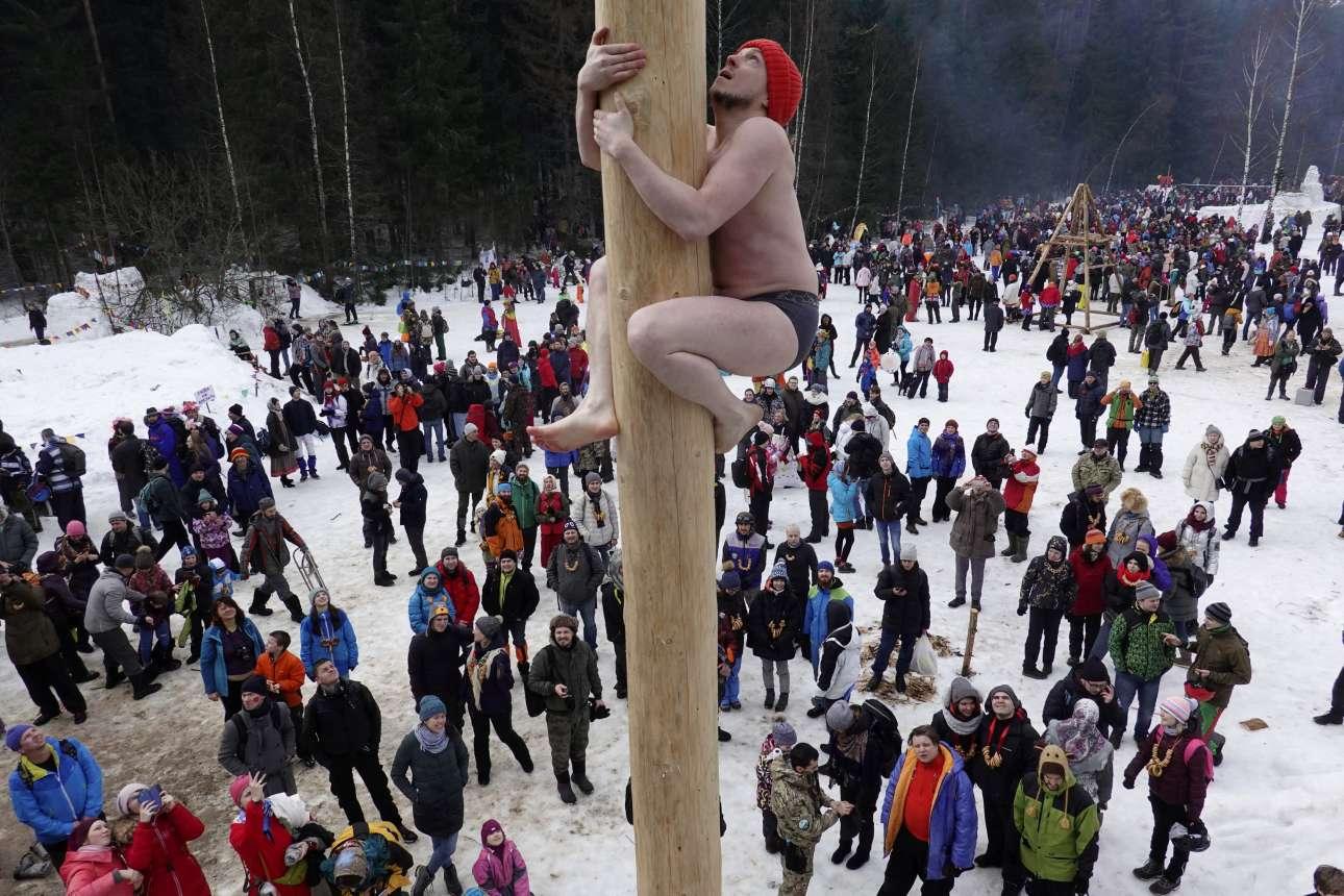 Ανδρας σκαρφαλώνει πάνω σε ξύλινο στύλο για να κερδίσει ένα βραβείο, έξω από τη Μόσχα