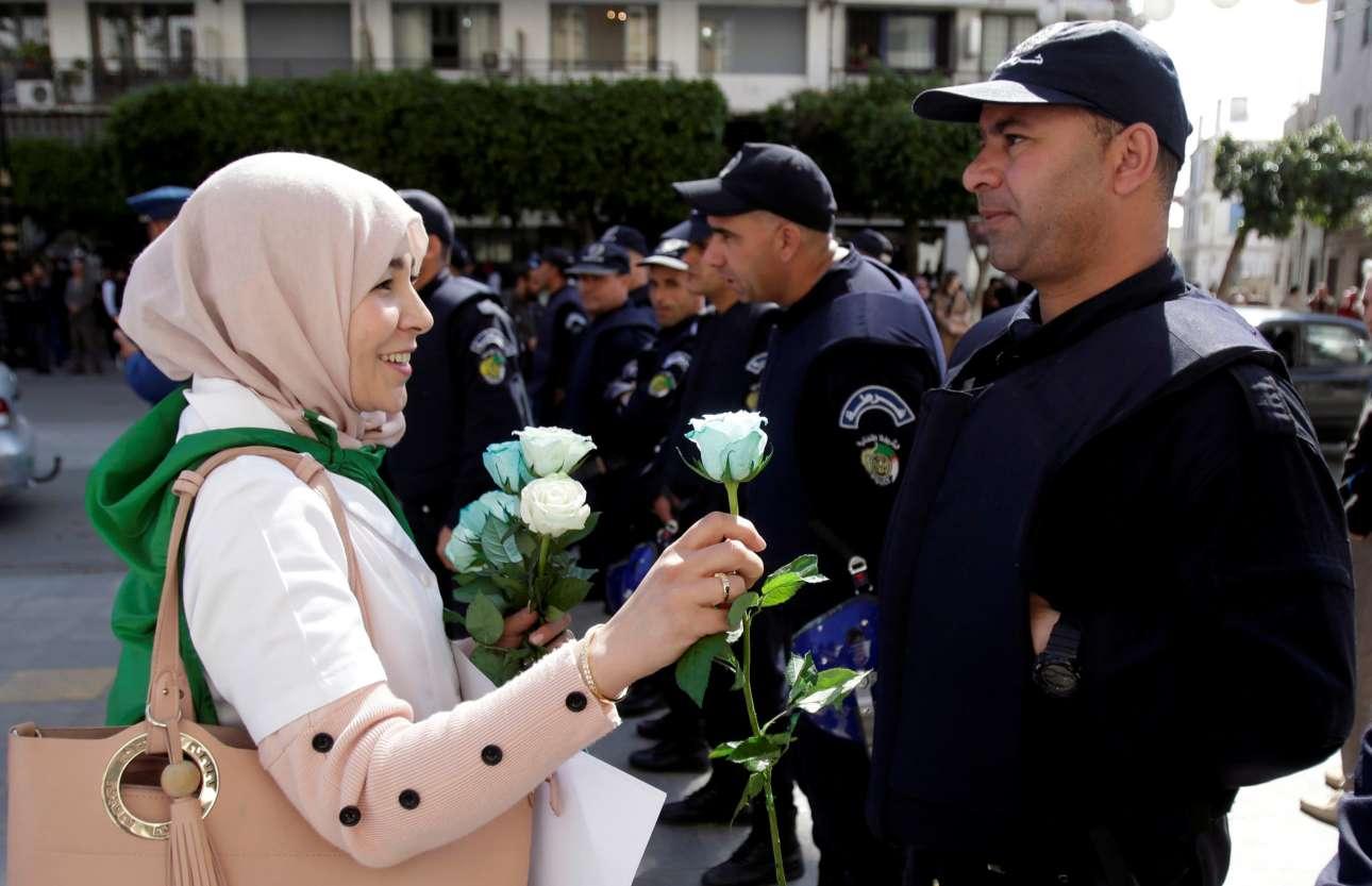 Τετάρτη, 13 Μαρτίου, Αλγερία. Κοπέλα που συμμετέχει στις διαδηλώσεις στο Αλγέρι απαιτώντας αλλαγή στην πολιτική κατάσταση της χώρας προσφέρει λουλούδια σε αστυνομικούς