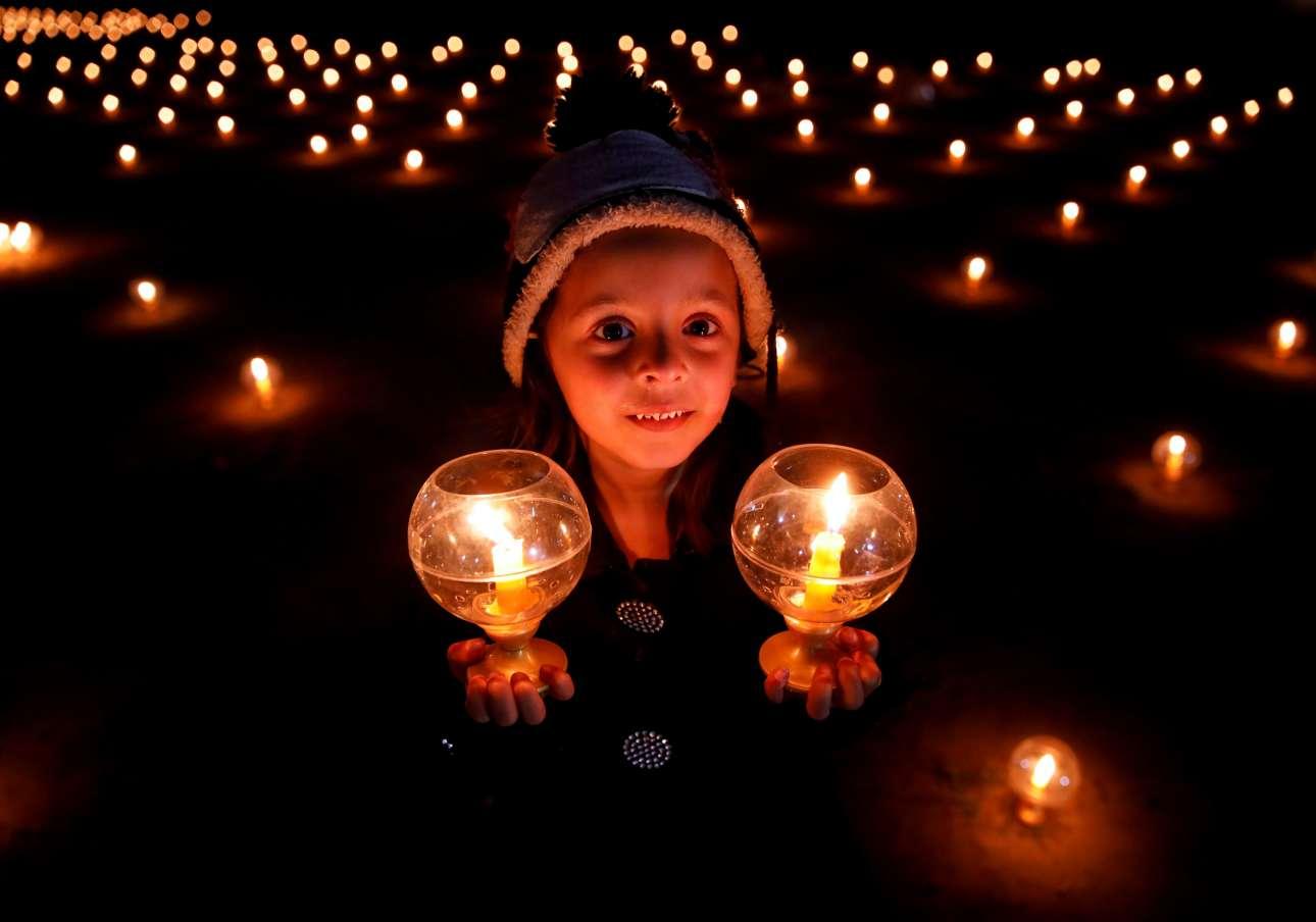 Σάββατο, 16 Μαρτίου, Νεπάλ. Κοριτσάκι κρατά δύο κεριά στο πλαίσιο της εκδήλωσης «Παγκόσμια ειρήνη δια μέσου της ειρήνης μέσα μας» στην πρωτεύουσα Κατμαντού