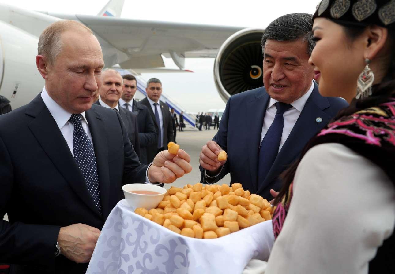 Πέμπτη, 28 Μαρτίου, Κιργιστάν. Ο πρόεδρος της Κιργιζίας Σοορονμπάι Τζεενμπέκοφ υποδέχεται το ρώσο πρόεδρο Βλαντίμιρ Πούτιν στο αεροδρόμιο του Μπισκέκ και τον κερνάει μια τοπική λιχουδιά