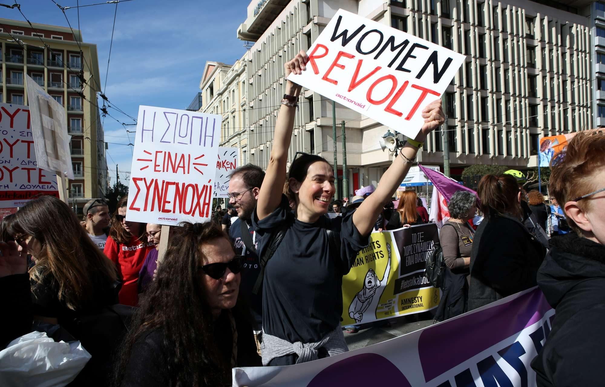 Οδός Σταδίου: Γυναίκες διαδηλώνουν στην Αθήνα το μεσημέρι της Παρασκευής, κρατώντας πλακάτ με τα συνθήματα «Η σιωπή είναι συνενοχή» και «Γυναίκες, επαναστατήστε»