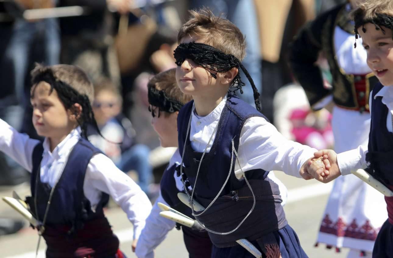 Παιδιά στη μαθητική παρέλαση στο Ηράκλειο με παραδοσιακές στολές. Ο μικρός στο κέντρο έχει ξαφνικό πρόβλημα οράσεως