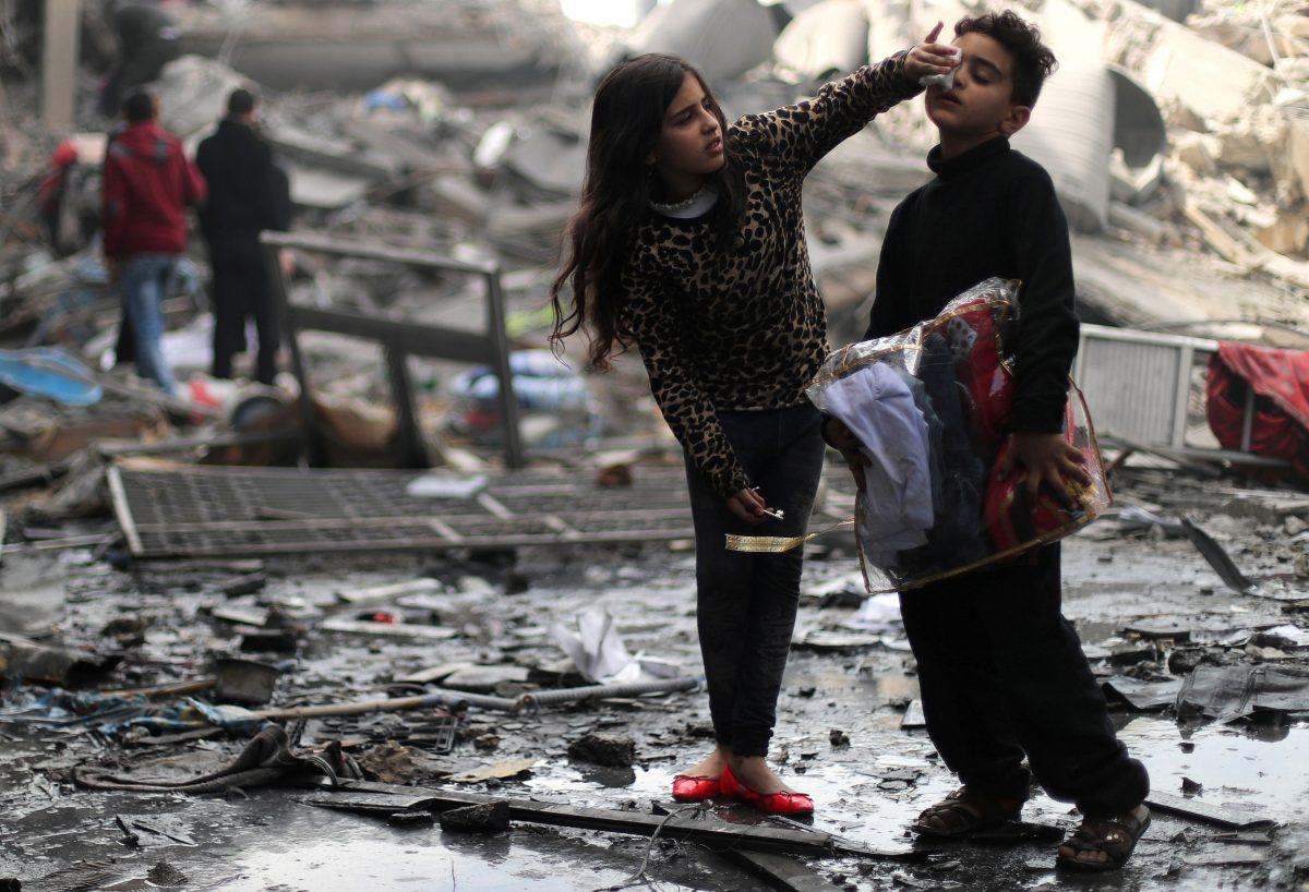 Τρίτη, 26 Μαρτίου, Γάζα. Μία μικρή Παλαιστίνια βοηθάει τον αδερφό της που έχει τραυματιστεί ελαφρά έξω από το κατεστραμμένο από ισραηλινά πλήγματα σπίτι τους