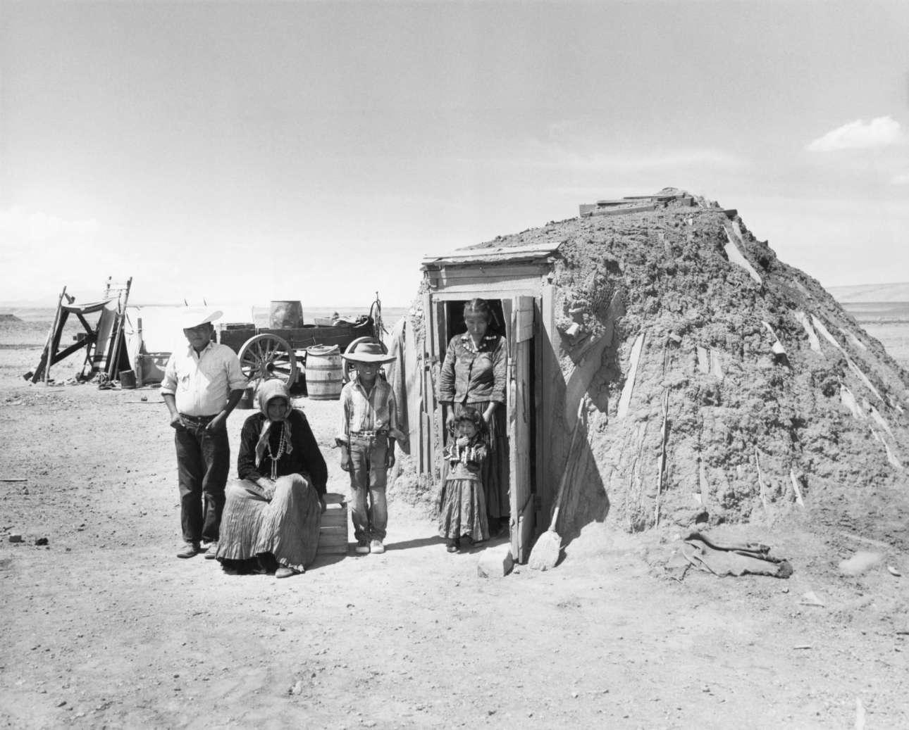 Οικογένεια Ναβάχο στέκονται έξω από το χόγκαν τους -την παραδοσιακή οικία της φυλής τους- κατά μήκος του νότιου άκρου του Grand Canyon
