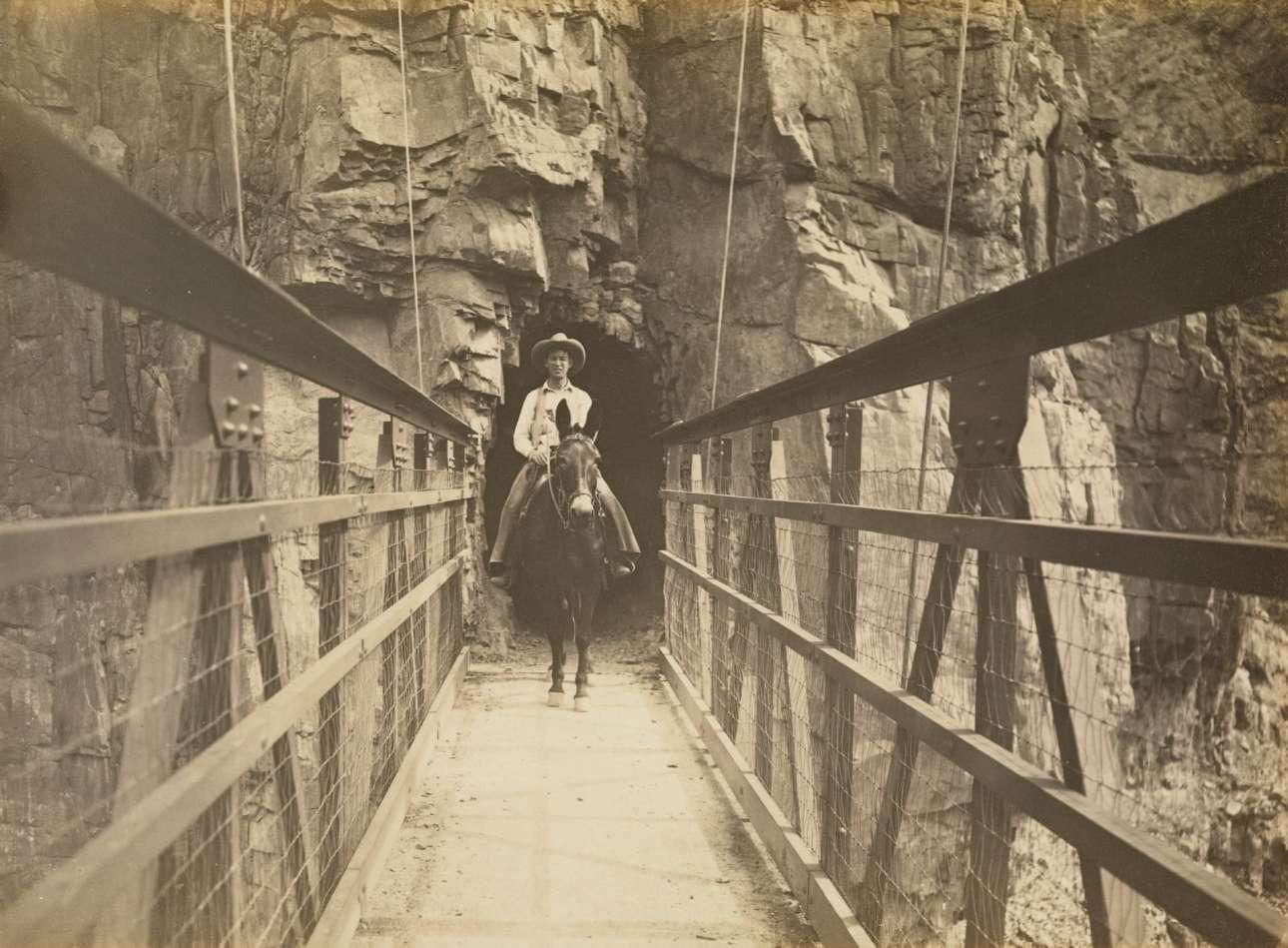 Ανδρας καβάλα σε μουλάρι διασχίζει την κρεμαστή γέφυρα Kaibab, το 1930