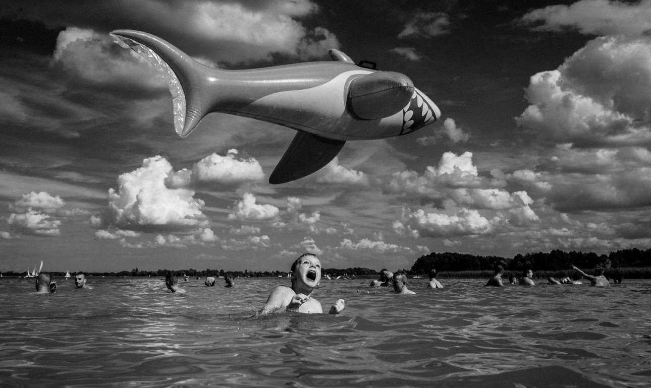 «SOS! Ιπτάμενος καρχαρίας», κατηγορία Ανθρωποι. Ενας φουσκωτός καρχαρίας «τρομοκρατεί» τους λουόμενους σε παραλία της Πολωνίας
