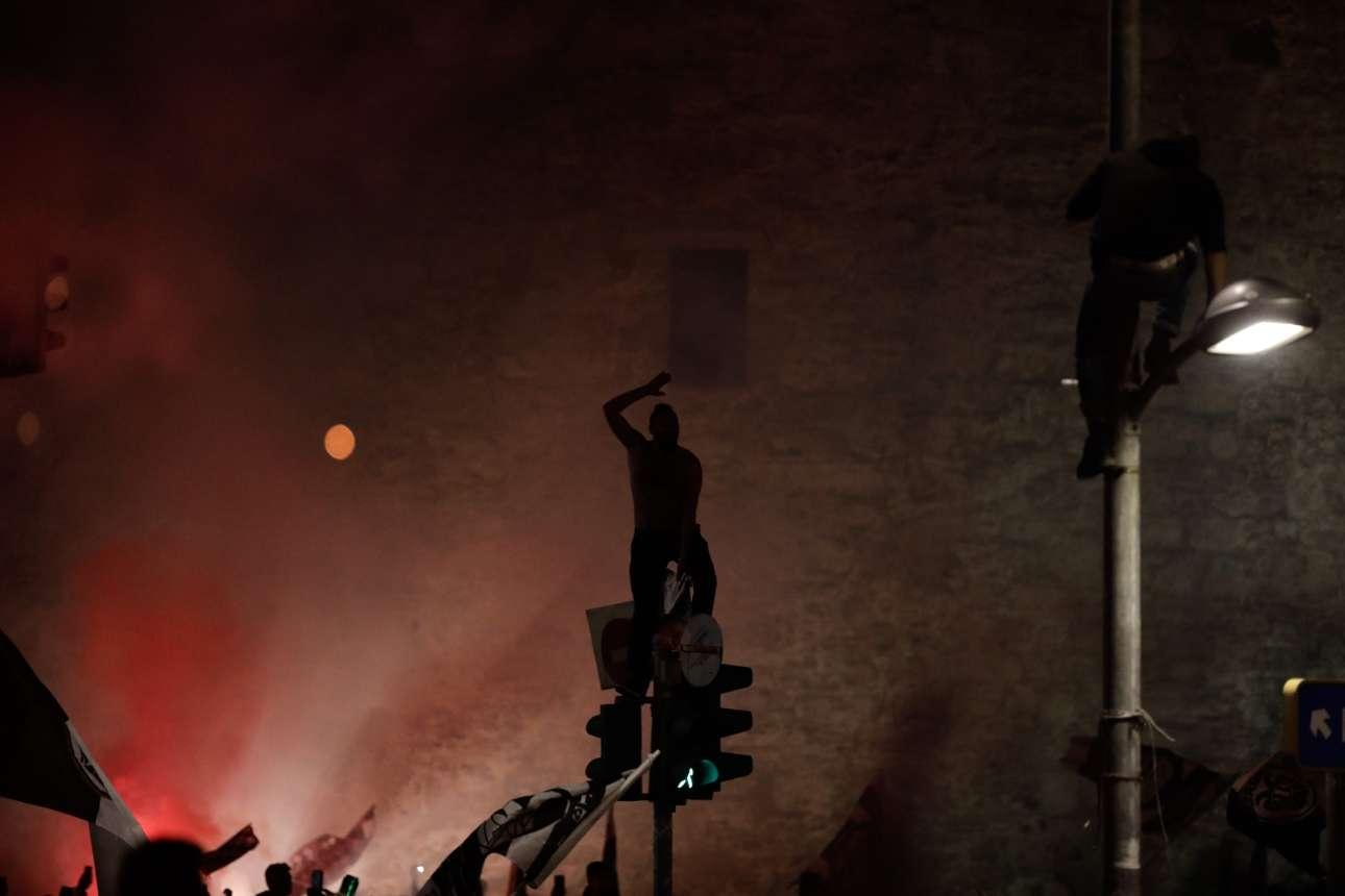 Οπαδοί έχουν ανέβει επάνω σε φωτεινούς σηματοδότες μπροστά από τον Λευκό Πύργο.