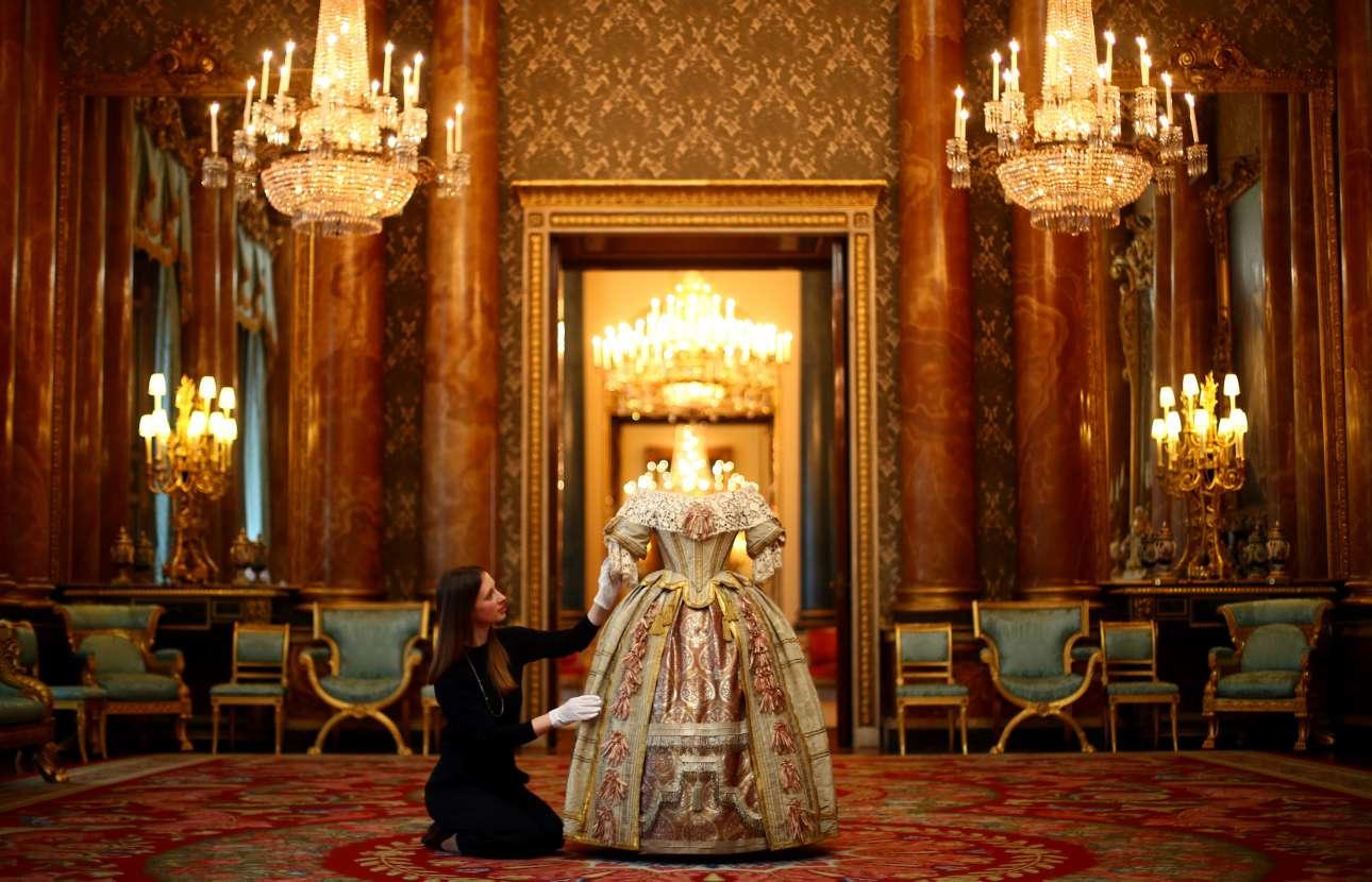 Τρίτη, 2 Απριλίου, Μεγάλη Βρετανία. Μέλος του προσωπικού του Ανακτόρου του Μπάκιγχαμ φροντίζει το εντυπωσιακό φόρεμα της βασίλισσας Βικτωρίας, το οποίο εκείνη φόρεσε στον Χορό των Στιούαρτ το 1851