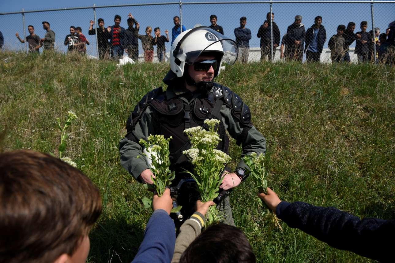 Παρασκευή, 5 Απριλίου, Ελλάδα. Προσφυγόπουλα προσφέρουν λουλούδια σε έναν αστυνομικό έξω από το κέντρο φιλοξενίας προσφύγων στα Διαβατά. Μία λάθος πληροφορία που διαδόθηκε μέσω Διαδικτύου προκάλεσε επεισόδια με εκατοντάδες πρόσφυγες και μετανάστες να προσπαθούν να σπάσουν τον αστυνομικό κλοιό προκειμένου να φτάσουν στα σύνορα
