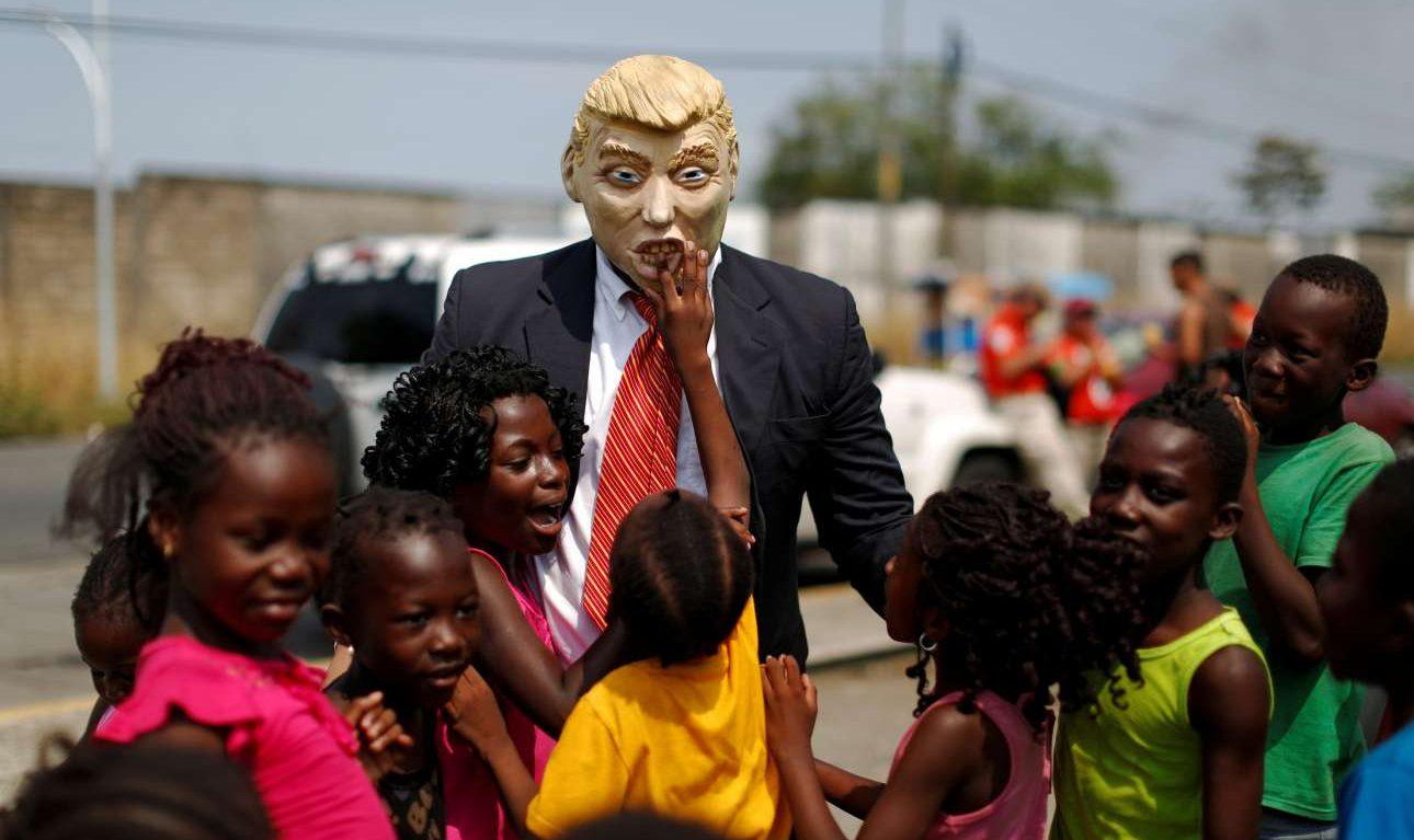 Σάββατο, 6 Απριλίου, Μεξικό. Ακτιβιστής με μάσκα και περιβολή Ντόναλντ Τραμπ παίζει με μικρά παιδιά, στο περιθώριο μίας διαμαρτυρίας έξω από το Εθνικό Ινστιτούτο Μετανάστευσης στην πόλη Ταπατσούλα, για το τείχος που θέλει να ανεγείρει ο πρόεδρος των ΗΠΑ
