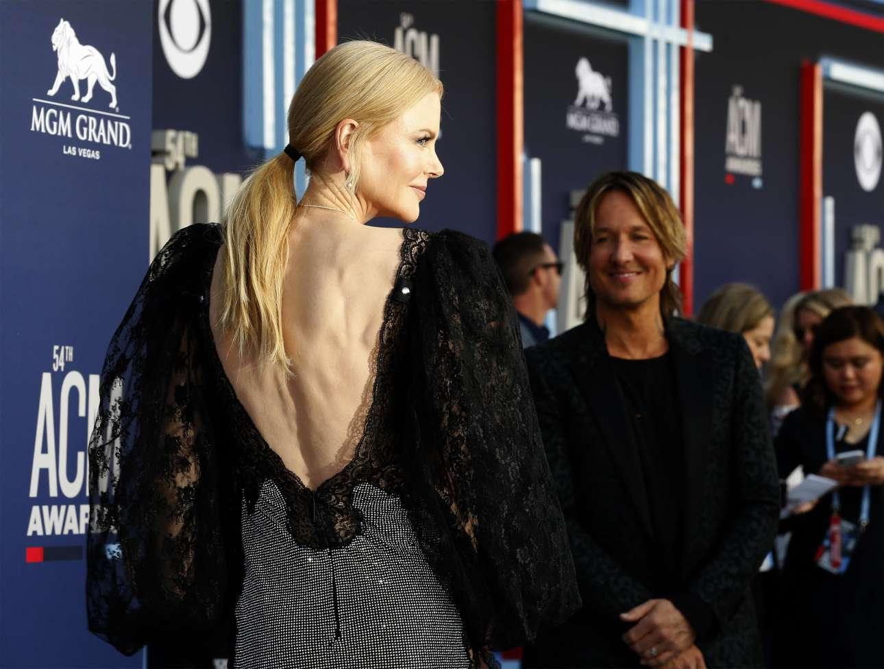 Δευτέρα, 8 Απριλίου, ΗΠΑ. Ο τραγουδιστής της κάντρι Κιθ Ερμπαν κοιτάζει την απαστράπτουσα σύζυγό του, Νικόλ Κίντμαν, κατά την άφιξή τους στα Μουσικά Βραβεία της κάντρι στο Λας Βέγκας