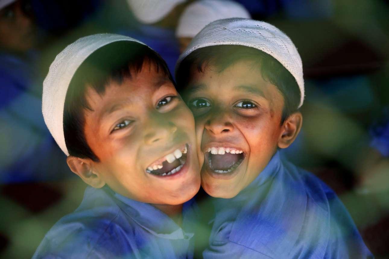 Τρίτη, 9 Απριλίου, Μπαγκλαντές. Δύο μικροί πρόσφυγες Ροχίνγκα, οι οποίοι φοιτούν σε ισλαμικό σχολείο στον προσφυγικό καταυλισμό στο Κοξ Μπαζάρ του Μπαγκλαντές, χαμογελούν στην κάμερα
