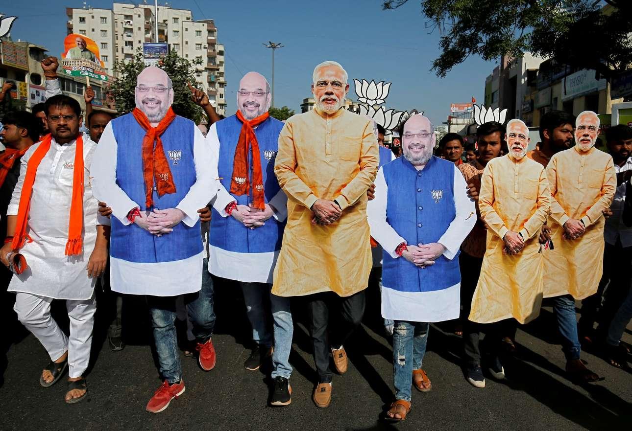Πέμπτη, 11 Απριλίου, Ινδία. Υποστηρικτές του κόμματος Μπαρατίγια Τζανάτα φορούν τις μάσκες του πρωθυπουργού Ναρέντρα Μόντι (στο κέντρο, με τα κίτρινα) και του προέδρου του κόμματος Αμίτ Σαχ κατά τη διάρκεια πορείας στην πόλη Αχμπανταμπάντ