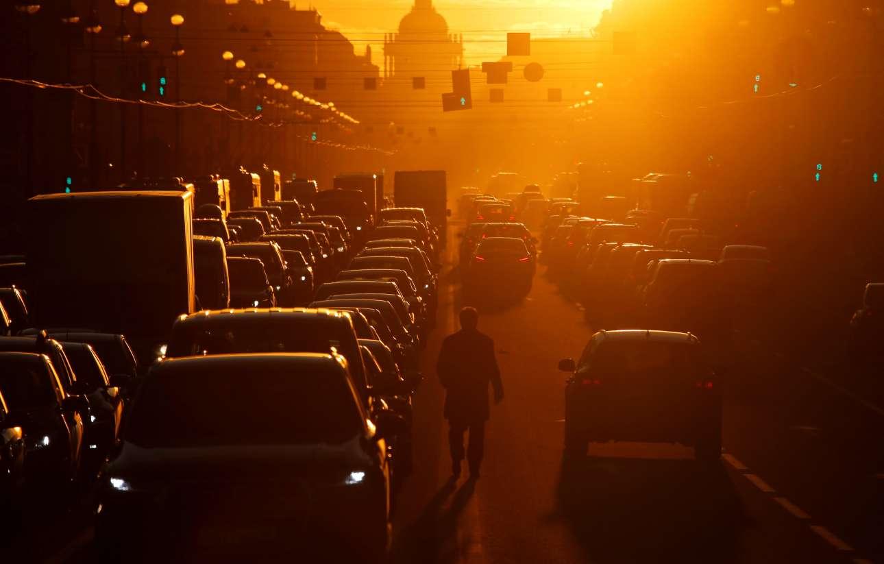 Παρασκευή, 12 Απριλίου, Ρωσία. Πεζός περπατά ανάμεσα στα ακινητοποιημένα από το μποτιλιάρισμα αυτοκίνητα στην Αγία Πετρούπολη