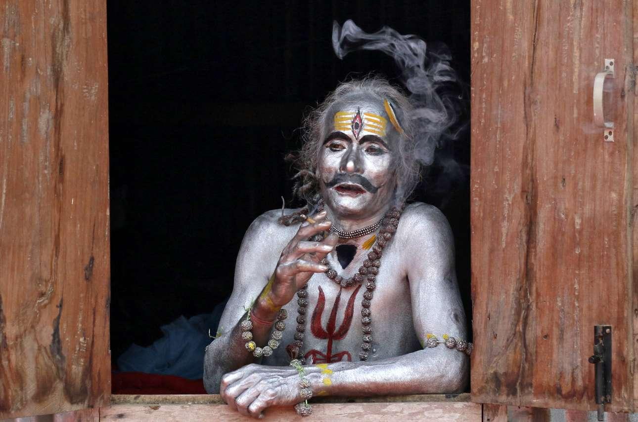 Σάββατο, 13 Απριλίου, Ινδία. Ανδρας με βαμμένο σώμα, καπνίζει ένα τσιγάρο περιμένοντας να λάβει μέρος στην θρησκευτική τελετή, κατά την διάρκεια του φεστιβάλ Γκατζάν