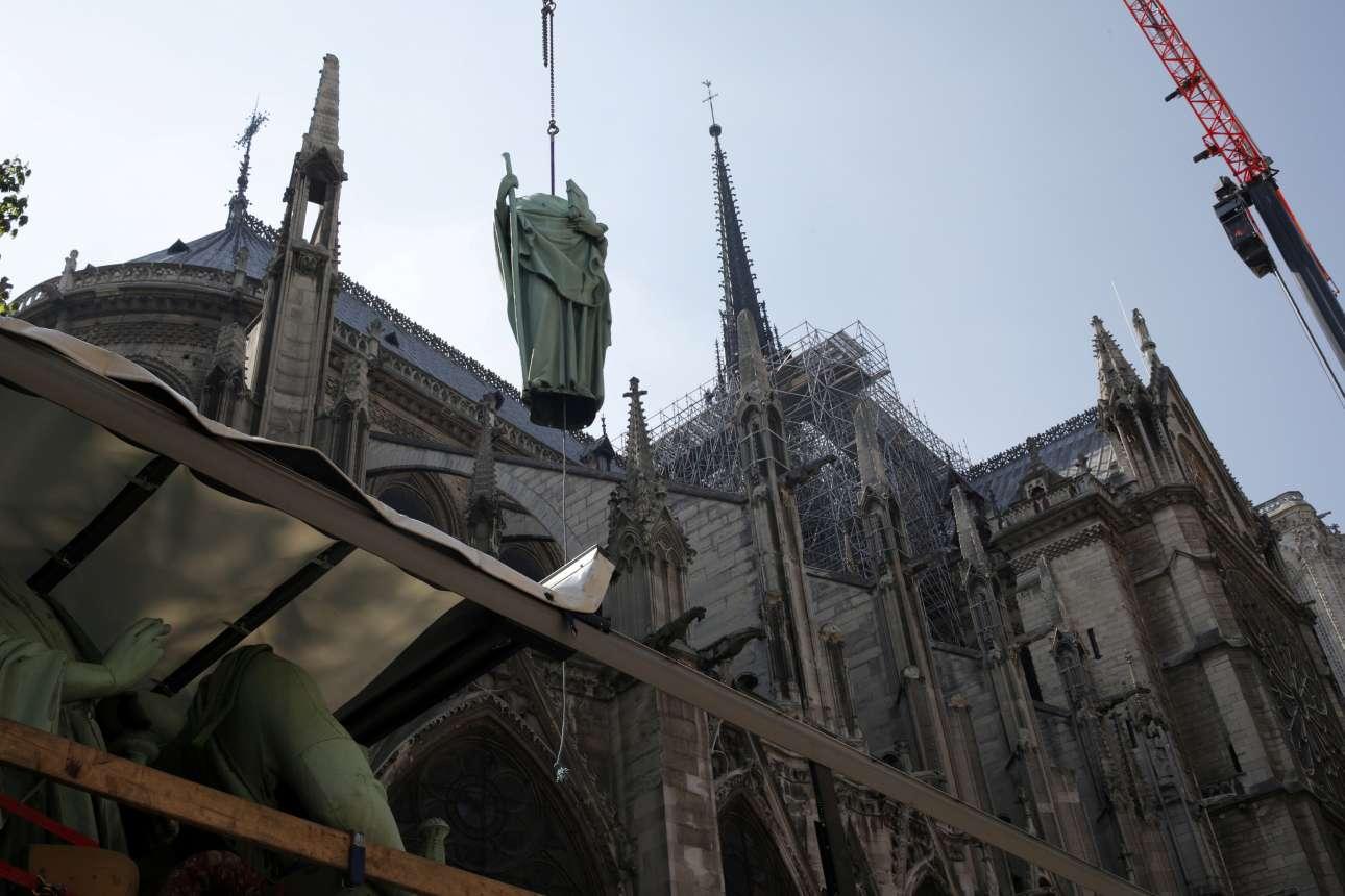 Ενα ακόμα άγαλμα κατεβαίνει από τη στέγη, τέσσερις ημέρες πριν την πυρκαγιά. Πίσω, δεξιά, φαίνεται το βέλος, που κατέρρευσε τη Δευτέρα
