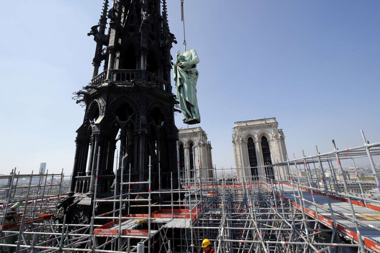 Ενα από τα «τυχερά» αγάλματα των 12 Αποστόλων, που πρόλαβαν να κατέβουν από την εξωτερική στέγη, τέσσερις ημέρες πριν την πυρκαγιά. Ενας εργάτης φαίνεται στη σκαλωσιά που περιστοιχίζει το περίφημο βέλος του ναού, τον πύργο, που κατέρρευσε τη Δευτέρα