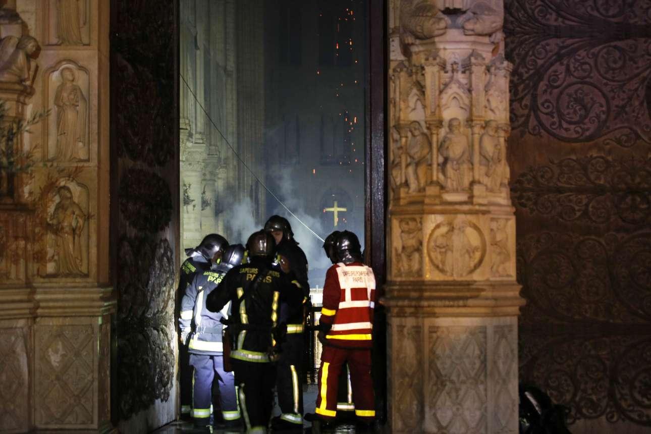 Πυροσβέστες κοιτούν στο εσωτερικό του ναού, από την κεντρική είσοδο. Στο βάθος, ο σταυρός πάνω από το ιερό