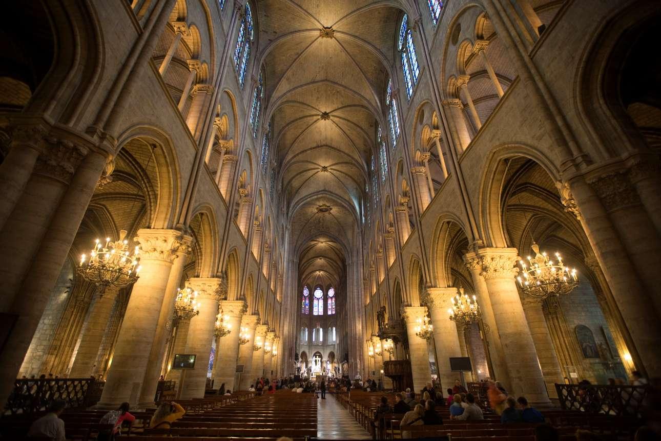 Τουρίστες θαυμάζουν το κατάφωτο εσωτερικό της Παναγίας των Παρισίων