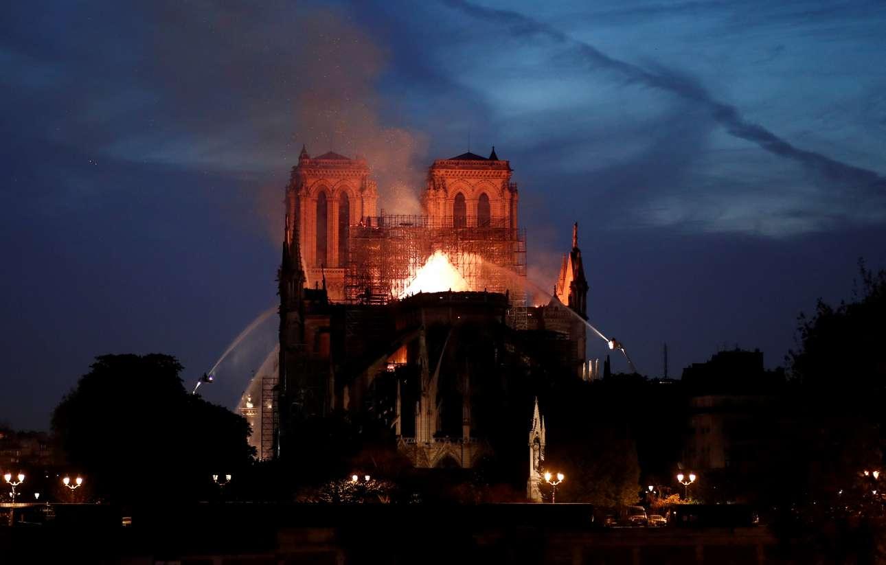 Οι φλόγες ξεπηδάνε από τη στέγη στο μέσο της Παναγίας των Παρισίων, πίσω από τα δύο χαρακτηριστικά πέτρινα κωδωνοστάσια, που τελικά διασώθηκαν