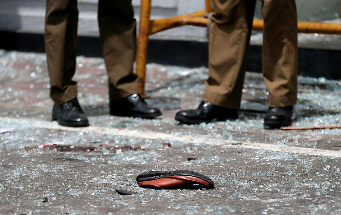 Αστυνομικοί στο σημείο της έκρηξης στο Νεγκόμπο την επομένη των επιθέσεων - τα προσωπικά είδη των πιστών είναι ακόμη εκεί