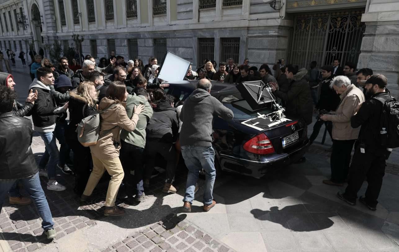 Μια σκηνή για την πρόσφατη πολιτική ιστορία του τόπου: κομπάρσοι ως νεολαίοι σπεύδουν ενθουσιασμένοι προς το πρωθυπουργικό αυτοκίνητο - ο Γαβράς δεξιά τσεκάρει το πλάνο