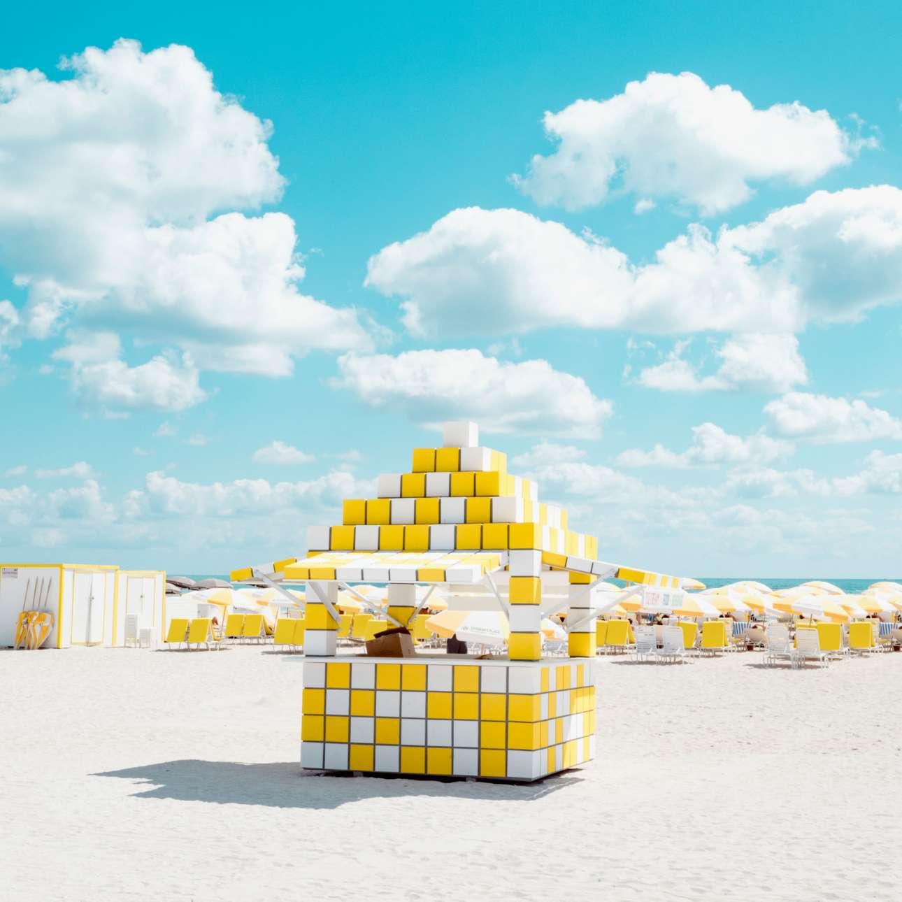 Ο Ντέβιντ Μπεχάρ εστιάζει στις καμπάνες στην παραλία του Μαϊάμι που μαζί με τις στολές των εργαζόμενων και τις ομπρέλες «δημιουργούν μία μικρή κοινότητα ταιριαστών χρωματικών αποχρώσεων»