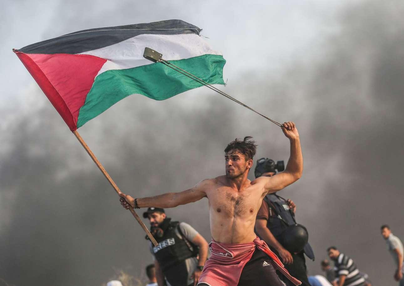Από τις πιο εμβληματικές φωτογραφίες της χρονιάς, ο νεαρός Παλαιστίνιος με τη σημαία και τη σφεντόνα στο χέρι διαδηλώνει κατά του ισραηλινού αποκλεισμού στη Γάζα, θυμίζοντας έντονα τον διάσημο πίνακα του Ντελακρουά