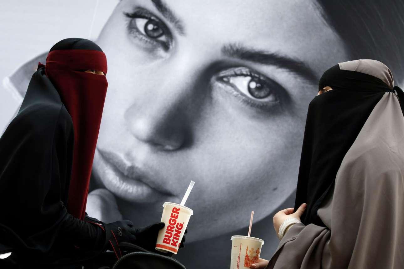 Δύο γυναίκες απολαμβάνουν τα ροφήματα τους από την αλυσίδα Burger King φορώντας νικάμπ σε εμπορικό κέντρο της Δανίας, λίγο πριν από την εφαρμογή της «απαγόρευσης της μπούρκας», του αμφιλεγόμενου νόμου που απαγορεύει στις γυναίκες να καλύπτουν το πρόσωπό τους