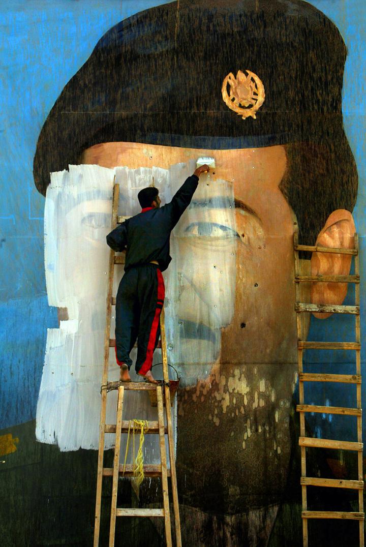 Βαγδάτη, Απρίλιος του 2003. Μία τοιχογραφία του Σαντάμ Χουσεΐν τρυπημένη από σφαίρες καλύπτεται με μπογιά, μετά την εισβολή των αμερικανικών στρατευμάτων