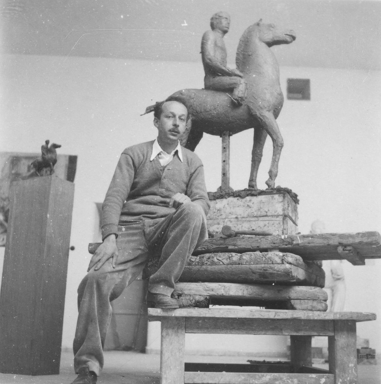Φωτογραφία του καλλιτέχνη στο εργαστήριό του στου Ζωγράφου δίπλα σε μελέτη για έφιππο γλυπτό, για τον Μέγα Αλέξανδρο