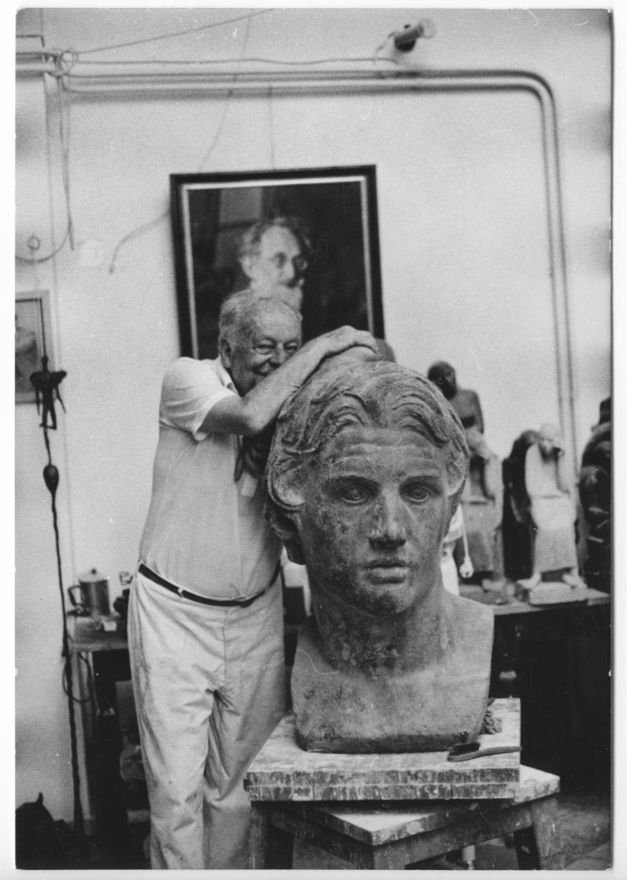 Ο Γιάννης Παππάς στο εργαστήριό του στου Ζωγράφου δίπλα στην μπρούτζινη προτομή του Μεγάλου Αλεξάνδρου. Ποζάρει δίπλα του με την οικειότητα ενός καλού φίλου. Αλλωστε, η πολύχρονη ενασχόληση είχε φέρει τον καλλιτέχνη κοντά στον στρατηλάτη