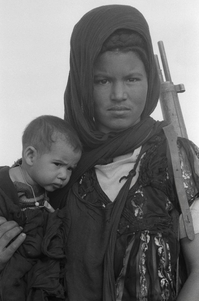 Δυτική Σαχάρα, Δεκέμβριος του 1976: γυναίκα αντάρτισσα του Μετώπου Πολισάριο με το παιδί της και το τουφέκι ανά χείρας. Το Πολισάριο πολεμούσε για την ανεξαρτητοποίηση των αυτόχθονων Σαχράουι από την μαροκινή και μαυριτανική κατοχή