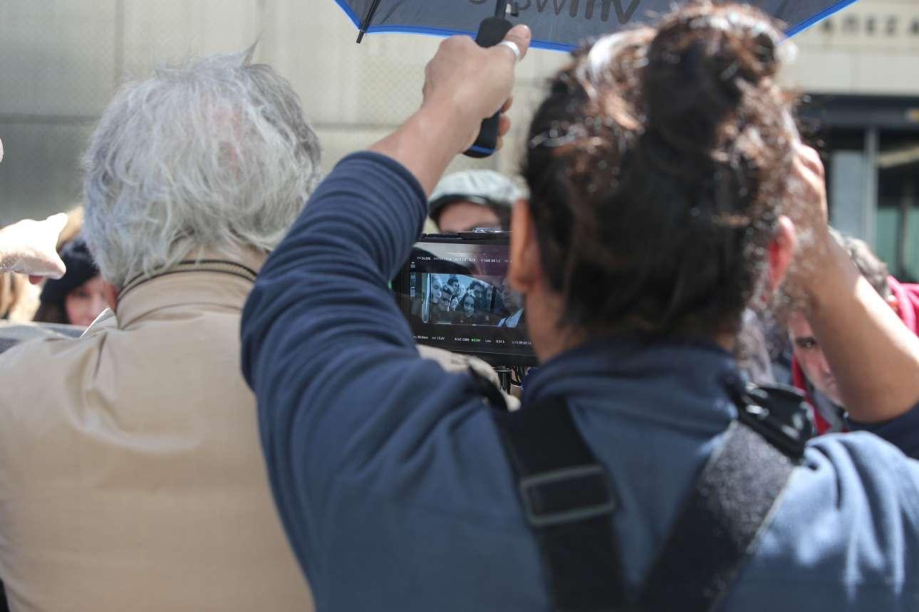 Ο Γαβράς βλέπει την εικόνα μέσα από την κάμερα - μια σκηνή όπου το πρωθυπουργικό όχημα, με τον Μπουρδούμη/Τσίπρα μέσα, δέχεται ένα κύμα ενθουσιασμένων νέων