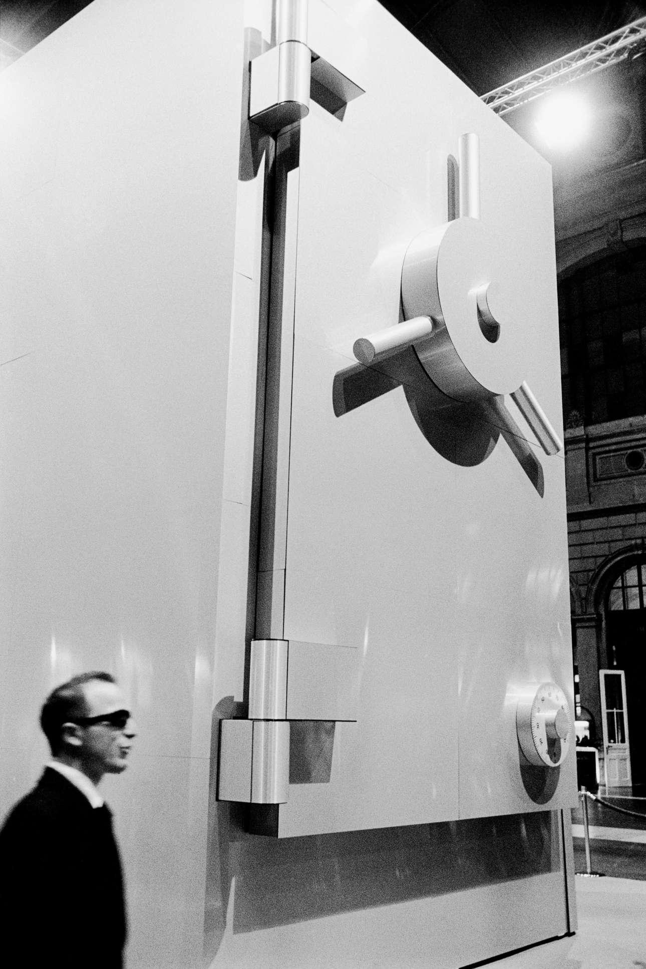 Φορώντας κοστούμι και γυαλιά, ο άνδρας στέκεται δίπλα σε ένα πελώριο ψεύτικο χρηματοκιβώτιο, στον κεντρικό σταθμό της Ζυρίχης