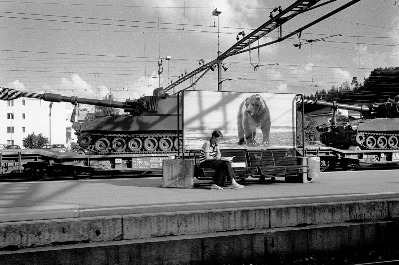 Σιδηροδρομικός σταθμός στη Ζυρίχη. Γυναίκα διαβάζει υπό το βλέμμα μιας «αρκούδας». Στο φόντο τρένο μεταφέρει δύο τανκς