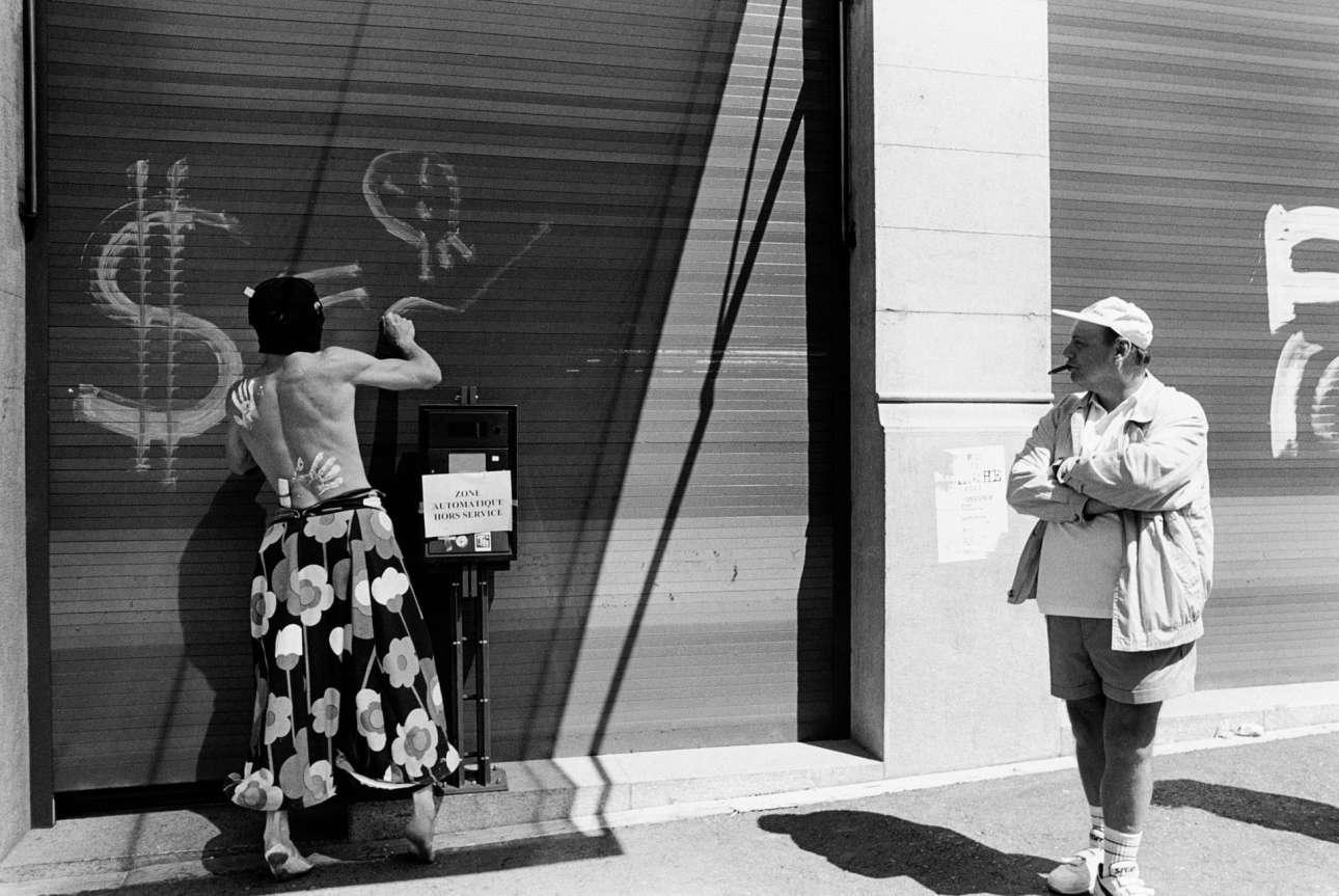 Διαμαρτυρία κατά συμφωνίας του Παγκοσμίου Οργανισμού Εμπορίου (WTO), το 1998. Ανδρας καπνίζει πούρο και παράλληλα παρακολουθεί έναν κουκουλοφόρο, γυμνόστηθο, ξυπόλητο διαδηλωτή με φλοράλ παρεό να κάνει γκραφίτι
