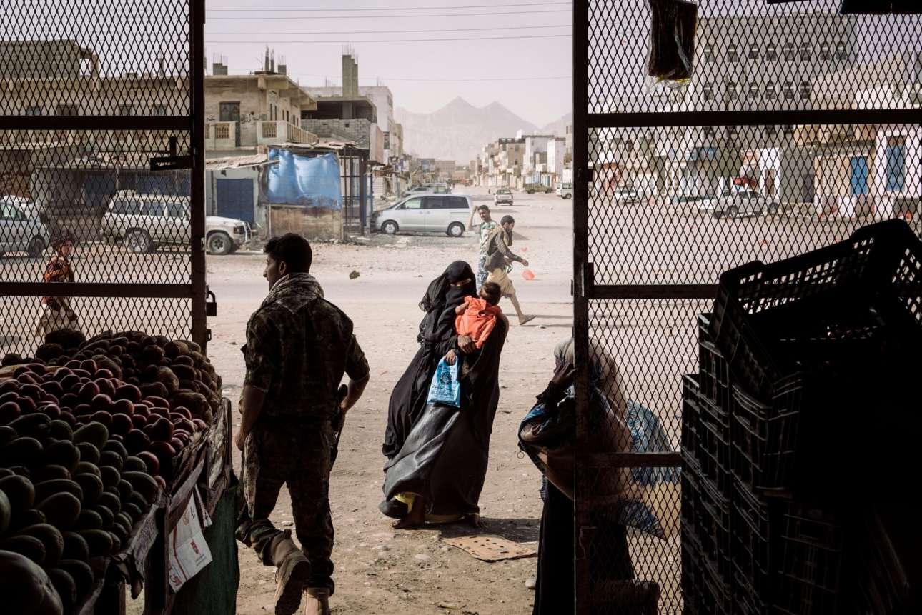 Πρώτη θέση στην κατηγορία Γενικές Ειδήσεις (Ιστορίες). Η κρίση στην Υεμένη: γυναίκα με μωρό στην αγκαλιά παρακαλάει για φαγητό έξω από μανάβικο στο χωριό Αζάν, το οποίο βρισκόταν υπό τον έλεγχο της Αλ Κάιντα μέχρι να ανακαταληφθεί από τις σαουδαραβικές ειδικές δυνάμεις, τον Δεκέμβριο του 2017. Τον τελευταίο χρόνο ο σκιώδης πόλεμος μεταξύ της Αλ Κάιντα και των ελεγχομένων από τη Σαουδική Αραβία ντόπιων μαχητών της Υεμένης επιτείνεται, αλλά μακριά από τα πρωτοσέλιδα