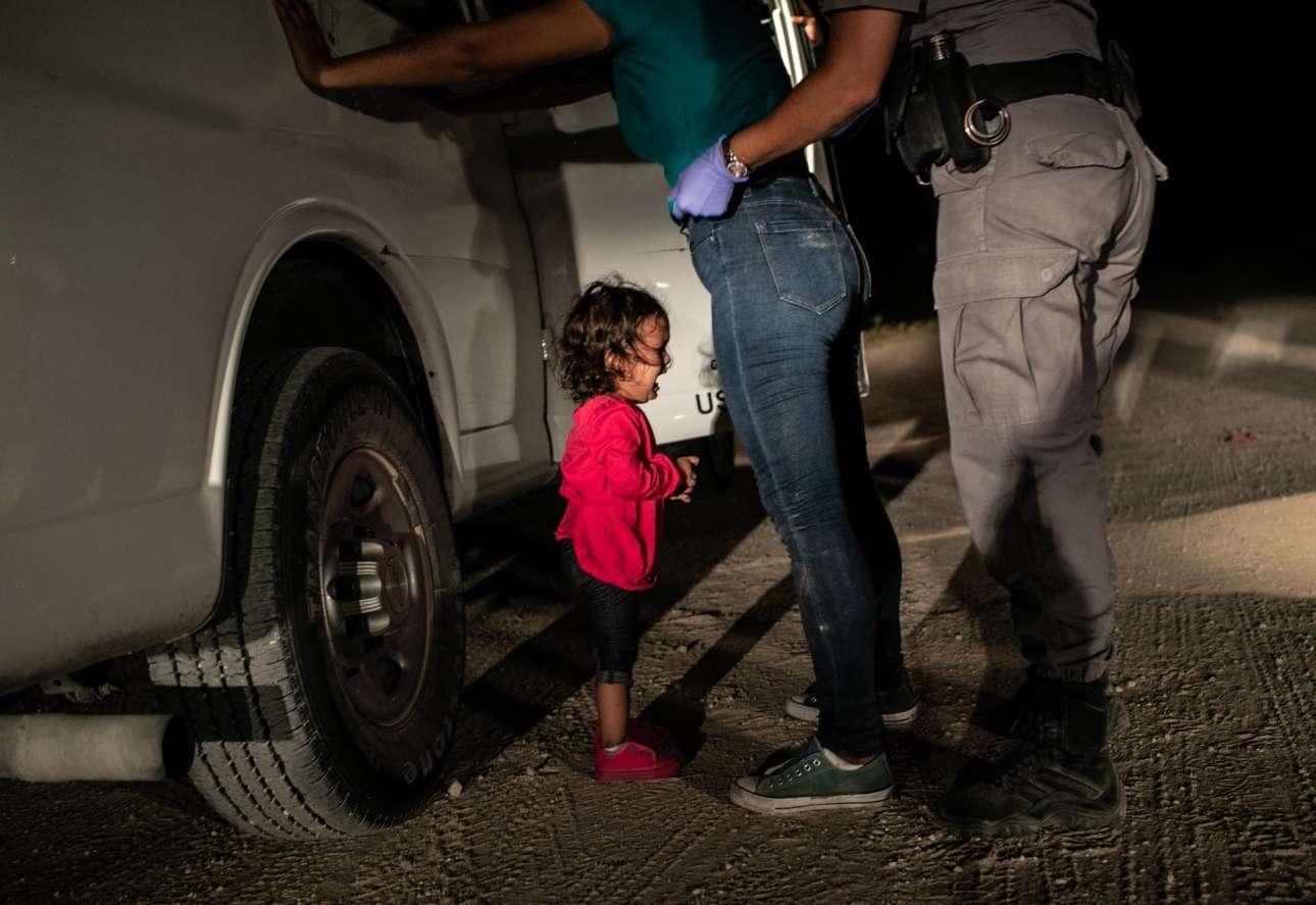 Νκητής του διαγωνισμού. Η δίχρονη Γιανέλα Σάντσες από την Ονδούρα κλαίει καθώς ένας φύλακας κάνει σωματικό έλεγχο στη μητέρα της στα σύνορα Μεξικού - ΗΠΑ, στο Τέξας. Επειτα από μία βδομάδα και γενική κατακραυγή, η κυβέρνηση Τραμπ σταμάτησε την αμφιλεγόμενη πολιτική που χώριζε τα παιδιά των μεταναστών από τους γονείς τους στα σύνορα