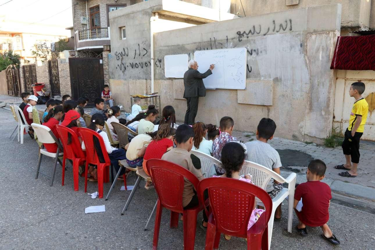 Δευτέρα, 6 Μαϊου, Ιράκ. Aυτοσχέδια σχολική τάξη σε δρόμο του Κιρκούκ. Ενας συνταξιούχος δάσκαλος παραδίδει αμισθί μαθήματα στα παιδιά της γειτονιάς του, σε μια πόλη που έχει πληγεί από τις πολεμικές συγκρούσεις του ιρακινού στρατού με αυτόν των Κούρδων