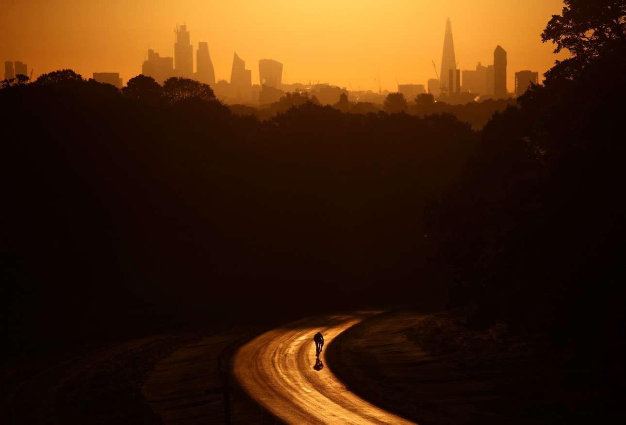 Ξημερώματα στο Λονδίνο και ένας ποδηλάτης διασχίζει το Πάρκο Ρίτσμοντ ενώ ο ήλιος ανατέλλει πάνω από τη βρετανική πρωτεύουσα