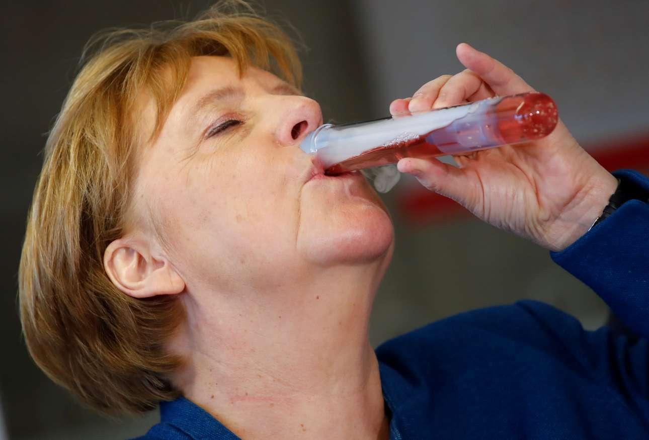 Η Ανγκελα Μέρκελ πίνει σε δοκιμαστικό σωλήνα ένα κοκτέιλ το οποίο ετοίμασαν νεαροί μαθητές στο Παιδικό Πανεπιστήμιο του Βούπερταλ στην Γερμανία