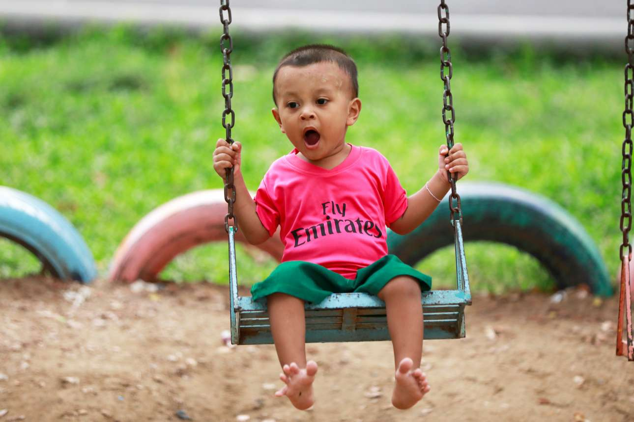 Μικρό αγοράκι φορώντας μπλούζα της Άρσεναλ κάνει κούνια σε παιδική χαρά στην Μπανγκόκ