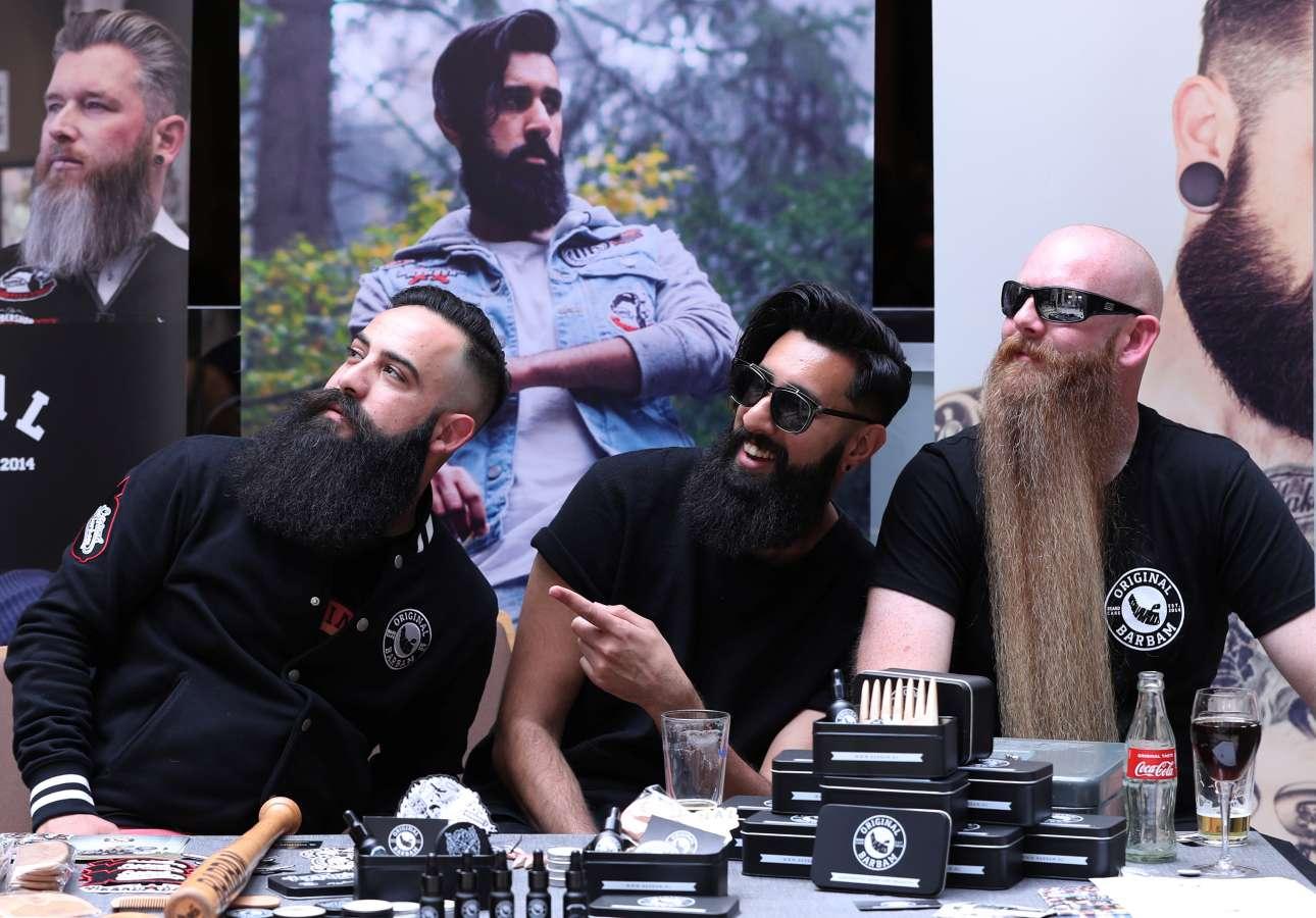 Οι τρεις άνδρες της φωτογραφίας φαίνεται πως εντοπίζουν κάτι ενδιαφέρον. Μπροστά τους διακρίνονται τα σύνεργα του αγαπημένου τους σπορ: η περιποίηση των τριχών