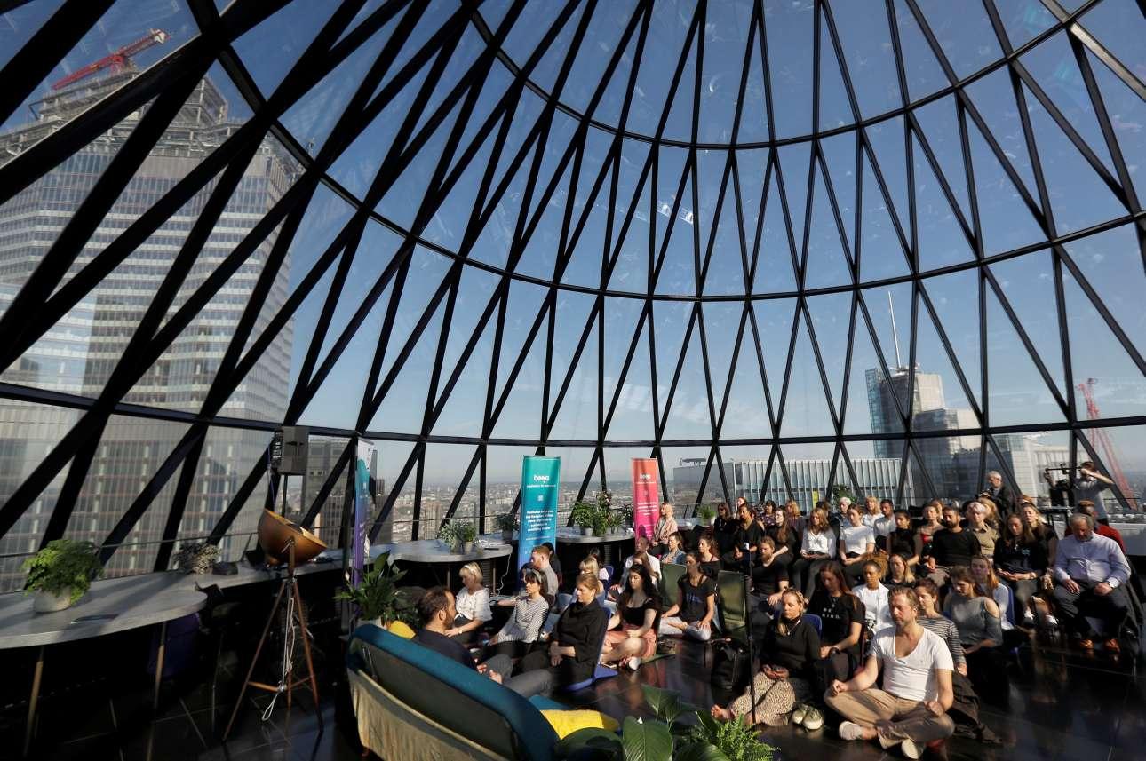 Κόσμος διαλογίζεται κατά την Παγκόσμια Ημέρα Διαλογισμού στο κτίριο «The Gherkin» του Λονδίνου