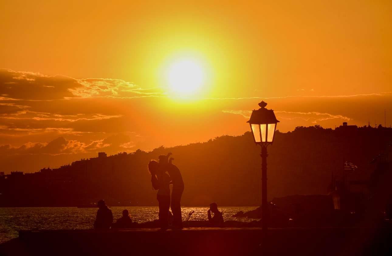 Ζευγάρι αγκαλιάζεται ενώ ο ήλιος δύει στην παραλία του Αλίμου