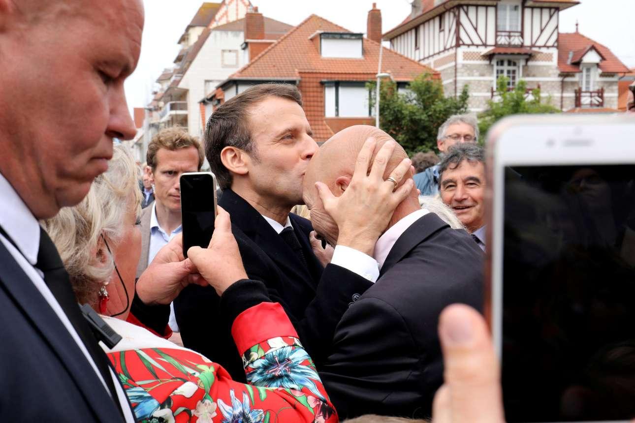 Λε Τουκέ, Γαλλία. Ο γάλλος πρόεδρος Εμανουέλ Μακρόν φιλά στο μέτωπο έναν υποστηρικτή του κόμματός του, αμέσως μετά την άσκηση του εκλογικού του δικαιώματος