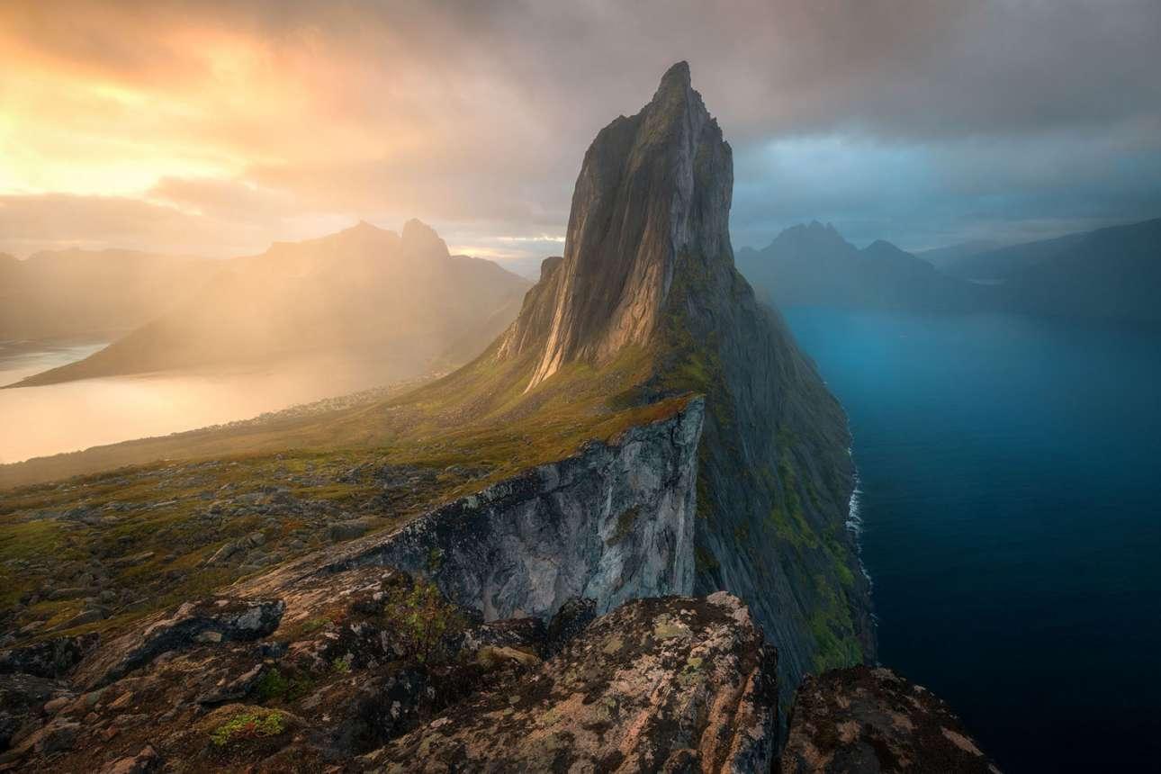 «Δυαδικότητα», βραβείο στην κατηγορία Τοπία, Υδάτινα Τοπία και Χλωρίδα. Αν και δεν είναι από τους γνωστούς προορισμούς της Νορβηγίας, το νησί Senja γίνεται ολοένα πιο δημοφιλές. Για αυτό ευθύνεται κυρίως ένα βουνό... Με ύψος περίπου 650 μέτρα πάνω από τη θάλασσα, η κορυφή του Σέγκλα είναι η επιτoμή της ανθεκτικότητας και της αγριάδας της βόρειας Νορβηγίας. Εδώ τάρανδοι περιφέρονται ελεύθεροι, ενώ φάλαινες, όρκες και θαλασσαετοί κυνηγούν ρέγγες στα στενά φιόρδ
