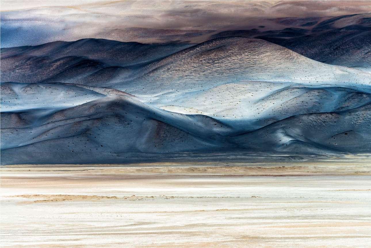 «Σύννεφα από αλάτι», βραβείο στην κατηγορία Τέχνη της Φύσης. Στις υψηλές πεδιάδες της βορειοδυτικής Αργεντινής, η φωτορεπόρτερ Κιάρα Σαλβαντόρι συνάντησε μια πραγματικά μαγική σκηνή. Σε υψόμετρο 3.500 μέτρων και περιστοιχισμένη από την άγρια ομορφιά του Salar de Antofalla -μία από τις μεγαλύτερες αλυκές στον κόσμο- παρακολουθούσε καθώς τα χρώματα του τοπίου άλλαζαν από τη σκίαση των νεφών που περνούσαν γρήγορα. Αυτό που ξεχωρίζει είναι η απουσία του ανθρώπου. Οι σκληρές συνθήκες επιτρέπουν σε ελάχιστους οργανισμούς να επιβιώσουν στην περιοχή, η οποία έτσι θα μπορέσει να προστατεύσει τη σουρεαλιστική ομορφιά της